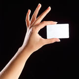 Hand holding card. Hand holding a blank card. Black background royalty free stock image
