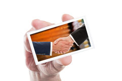 Hand holding card with business handshake over wooden wall Royalty Free Stock Photos