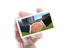 Hand holding card with real estate handshake. With city background Stock Images