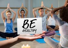 Hand holding card with text be healthy in yoga class. Digital composition of hand holding card with text be healthy in yoga class Stock Images