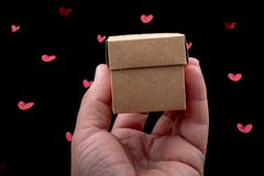 Hand holding cardboard Box on a background with hearts. Hand holding cardboard box on black background with red hearts royalty free stock photography