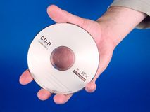 A hand holding a CD. A hand holding a blank CD royalty free stock photo