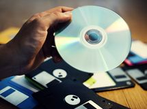Hand holding CD disk background with floppy on the table Stock Images