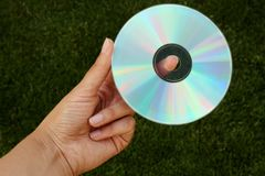 Hand holding CD in front of green bokeh background made out of grass. Technology and nature royalty free stock images