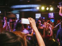Hand holding Cell phone Blank screen Photo shot Blur Concert Royalty Free Stock Photo