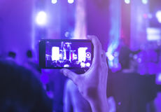 Hand holding Cell phone Camera photo shot on Concert. Event Crowd people Royalty Free Stock Images