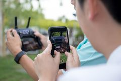 Hand holding cell phone recording video at radio control drone. In blur background Stock Images