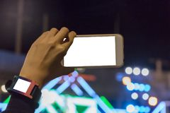Hand holding cell phone to recording in concert. With many lighting on front stage, blank screen on white Royalty Free Stock Image