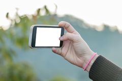 Hand holding cell phone to take a photo, blank screen on white royalty free stock image
