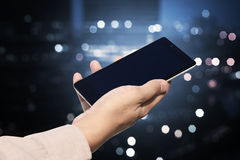 Hand holding cellphone with blank screen on blurry night city Stock Photo