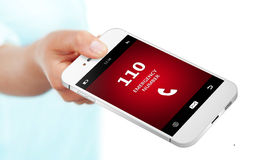 Hand holding cellphone with emergency number 110 Royalty Free Stock Image