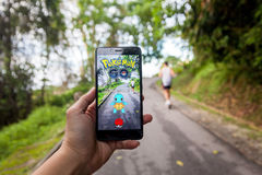 Hand holding a cellphone playing Pokemon Go. California, United States, 23 July 2016 : Hand holding a cellphone playing Pokemon Go game in footpath Stock Photography