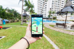 Hand holding a cellphone playing Pokemon Go. California, United States, 16 July 2016 : Hand holding a cellphone playing Pokemon Go game in garden stock photos