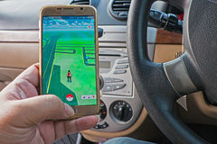 Hand holding cellphone playing pokemon go while driving a car is dangerous and prohibited Stock Photos