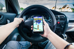 Hand holding a cellphone playing Pokemon Go game while driving Stock Photography