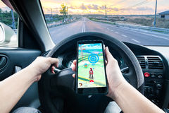 Hand holding a cellphone playing Pokemon Go game while driving Stock Photos