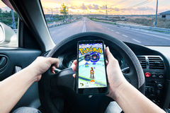 Hand holding a cellphone playing Pokemon Go game while driving Royalty Free Stock Photos