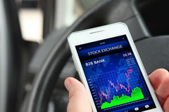Hand holding cellphone with stock exchange screen Royalty Free Stock Images