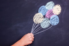 Hand holding chalk drawing balloons royalty free stock photo