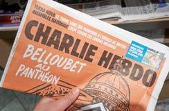 A hand holding Charlie Hebdo newspaper. stock photo