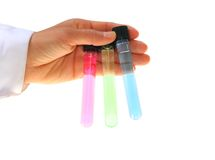 Hand holding chemistry tubes. Hand holding three chemistry tubes with light coloured liquids inside. Colors are red, green and blue. Part of a laboratory coat Royalty Free Stock Photo