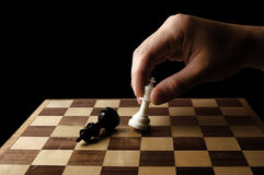 Hand holding a chess piece on black background. Close-up photography Stock Photography