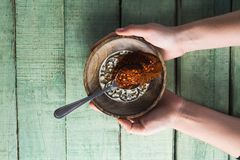Hand holding chili powder and crushed red pepper in bowl Stock Photos
