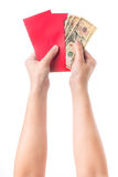 Hand holding chinese red envelope with money isolated over white background. Royalty Free Stock Photos