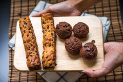 Hand holding  Chocolate chip stick bread with muffin on A cuttin Stock Images