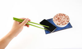 Hand holding chopsticks brown rice and smartphone.Eat the food, Royalty Free Stock Photos