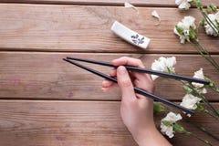 Hand holding chopsticks Stock Photos