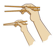 Hand holding chopsticks Royalty Free Stock Photos