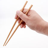 Hand holding chopsticks Stock Images