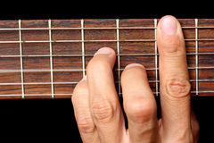 Hand holding a chord, and vibrating strings Royalty Free Stock Images