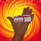 Hand holding a Christmas gift over red and yellow background Stock Photo