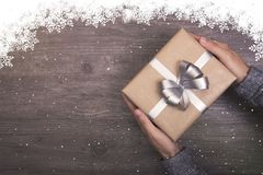 Hand holding Christmas presents gift on wooden table background and snowing fall winter. Royalty Free Stock Images
