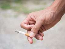 Hand Holding Cigarette While Smoking Stock Images