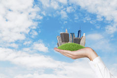 Hand holding  city. Hand holding city on green grass hill Stock Photography