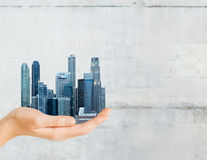 Hand holding city over gray concrete background Royalty Free Stock Images