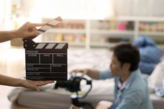Hand holding clapper board on blurred movie director. Entertainment for movie concept stock images
