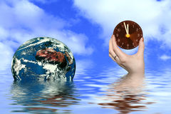 Hand holding clock and earth Stock Photo