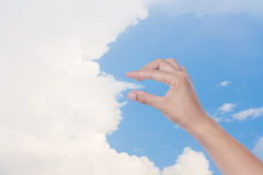 Hand holding clouds. The appearance of a hand holding a cloud in the sky Royalty Free Stock Photo