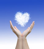 Hand holding with clouds heart image on blue Royalty Free Stock Image