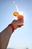 Hand holding a cocktail tequila sunrise. On the background of the sea with luxury yacht on the horizon Stock Photo