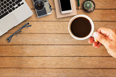 Hand holding coffee cup with office equipment Stock Photography