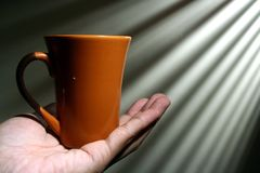 Hand holding a coffee mug Stock Photos