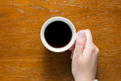 Hand holding coffee on the table Stock Photo