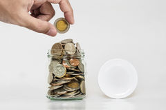 Hand holding coin with jar glass full of coins, and jar cap with copy space Royalty Free Stock Photography