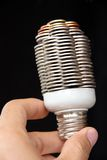 Hand holding coin light bulb Royalty Free Stock Images
