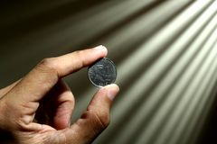 Hand holding a coin Stock Images